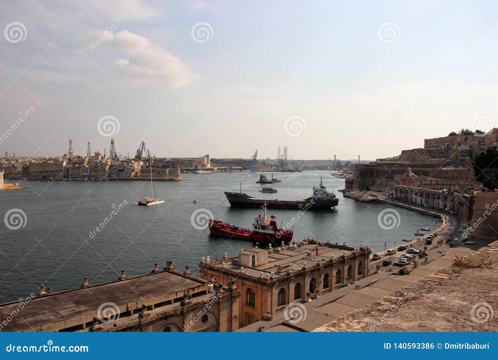 Valletta, Malta, em agosto de 2015 Opinião magnífica do mar do porto principal dos island's com navios de carga