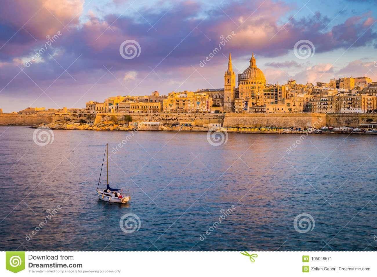 Valletta, Malta - St.Paul`s Cathedral in golden hour at Malta`s capital city Valletta with sailboat and beautiful colorful sky