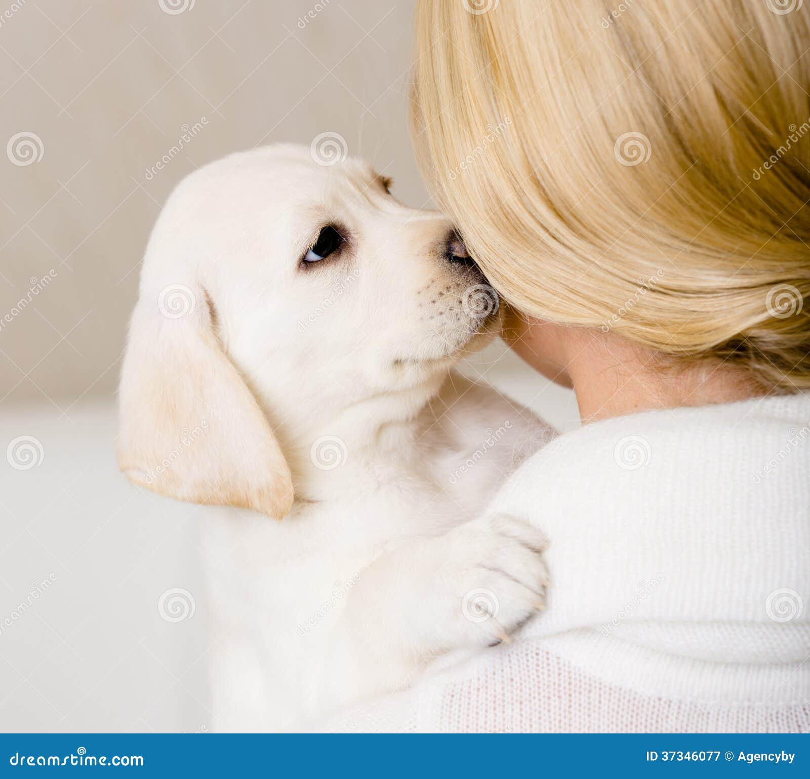 Valpen kysser framsidan av kvinnan