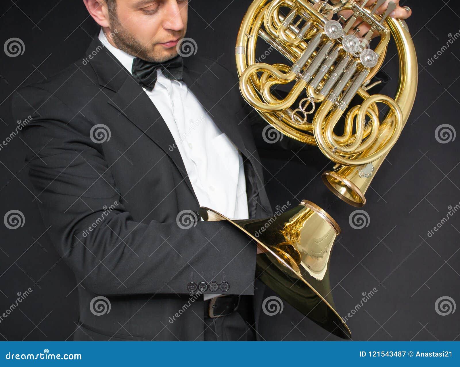 Valthornspelare Horn för musikinstrument i händerna av mannen för hornist A i en dräkt och i en fjäril med ett musikinstrument