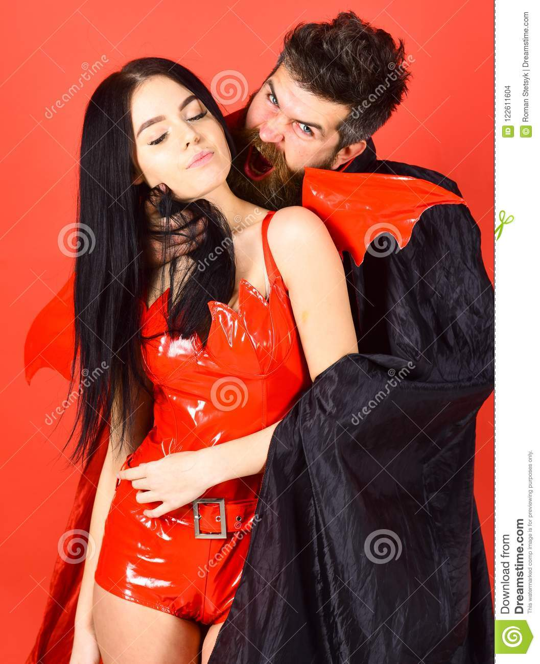 Vampire bites female neck. Couple in love play role game. Vampires victim concept. Man and woman dressed like vampire
