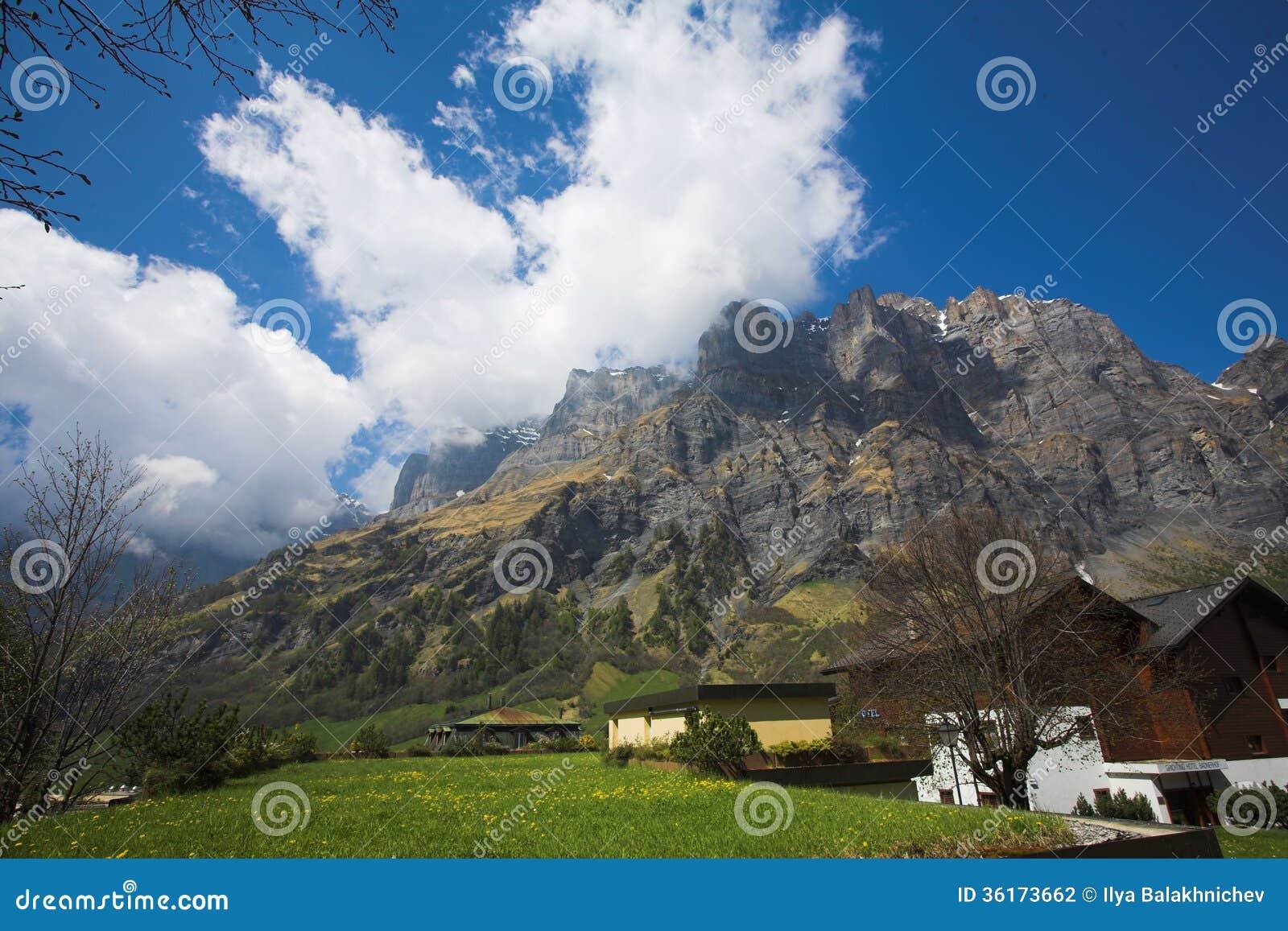 Van de de berghemel van luekerbadzwitserland de blauwe houten huizen stock fotografie - De mooiste gevels van huizen ...
