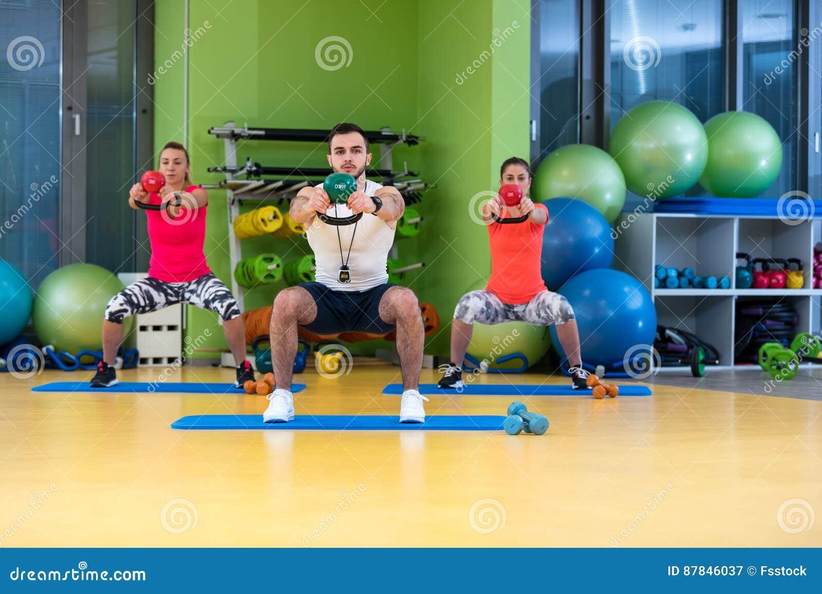 Van de de oefeningsman en vrouw van de Kettlebellsschommeling training bij gymnastiek