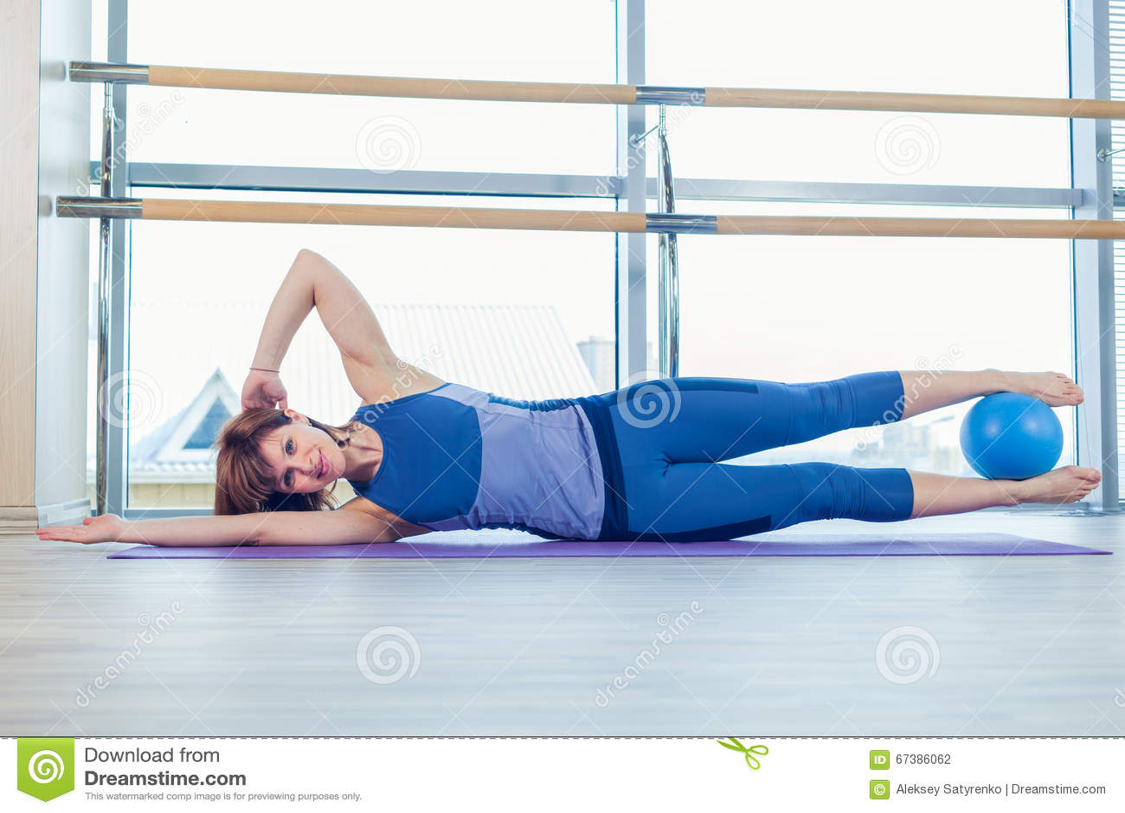 Van de de stabiliteitsbal van de Pilatesvrouw de oefeningstraining bij gymnastiek binnen