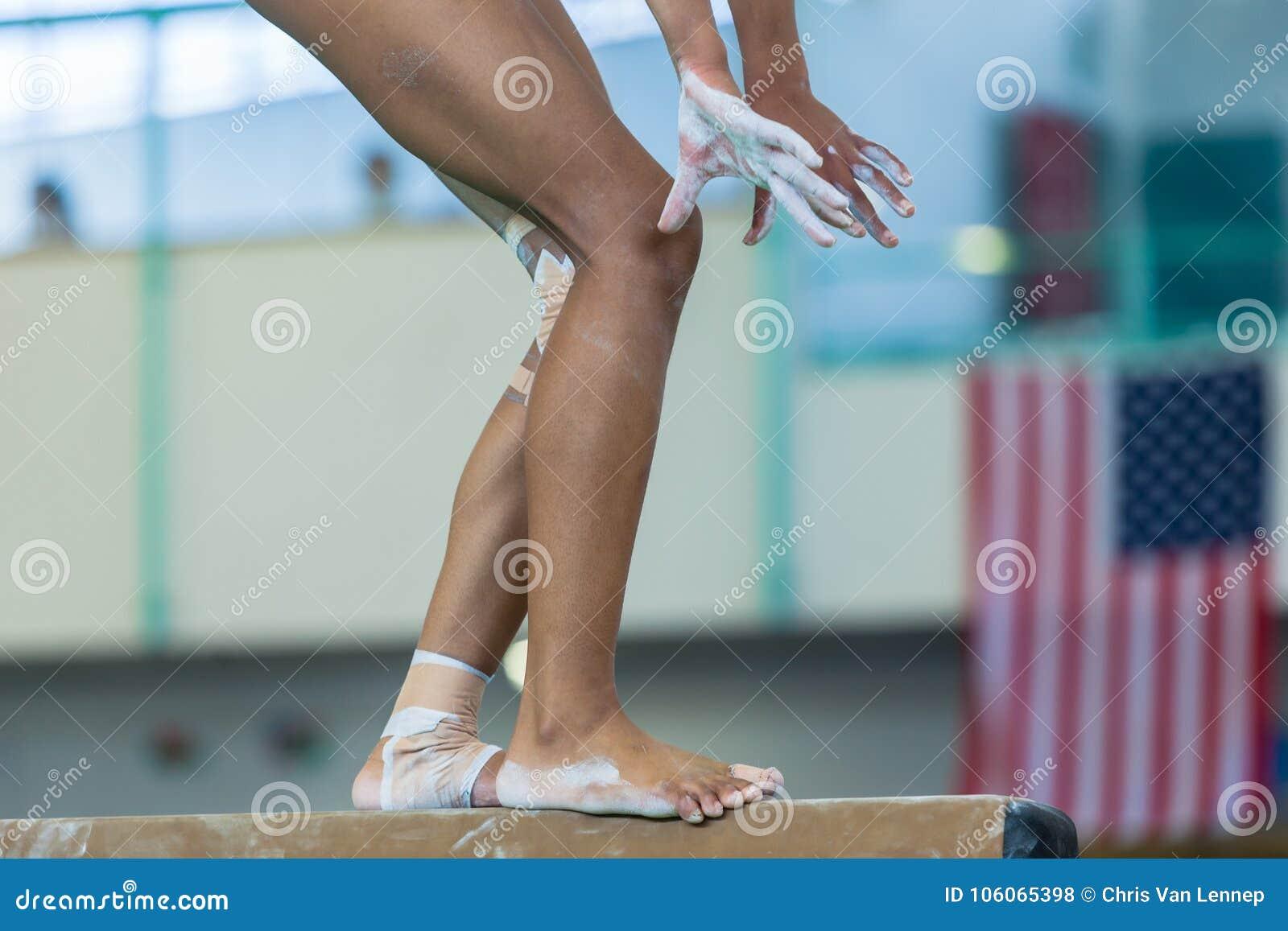 Van de de Evenwichtsbalkclose-up van het gymnastiekmeisje de Benenhanden