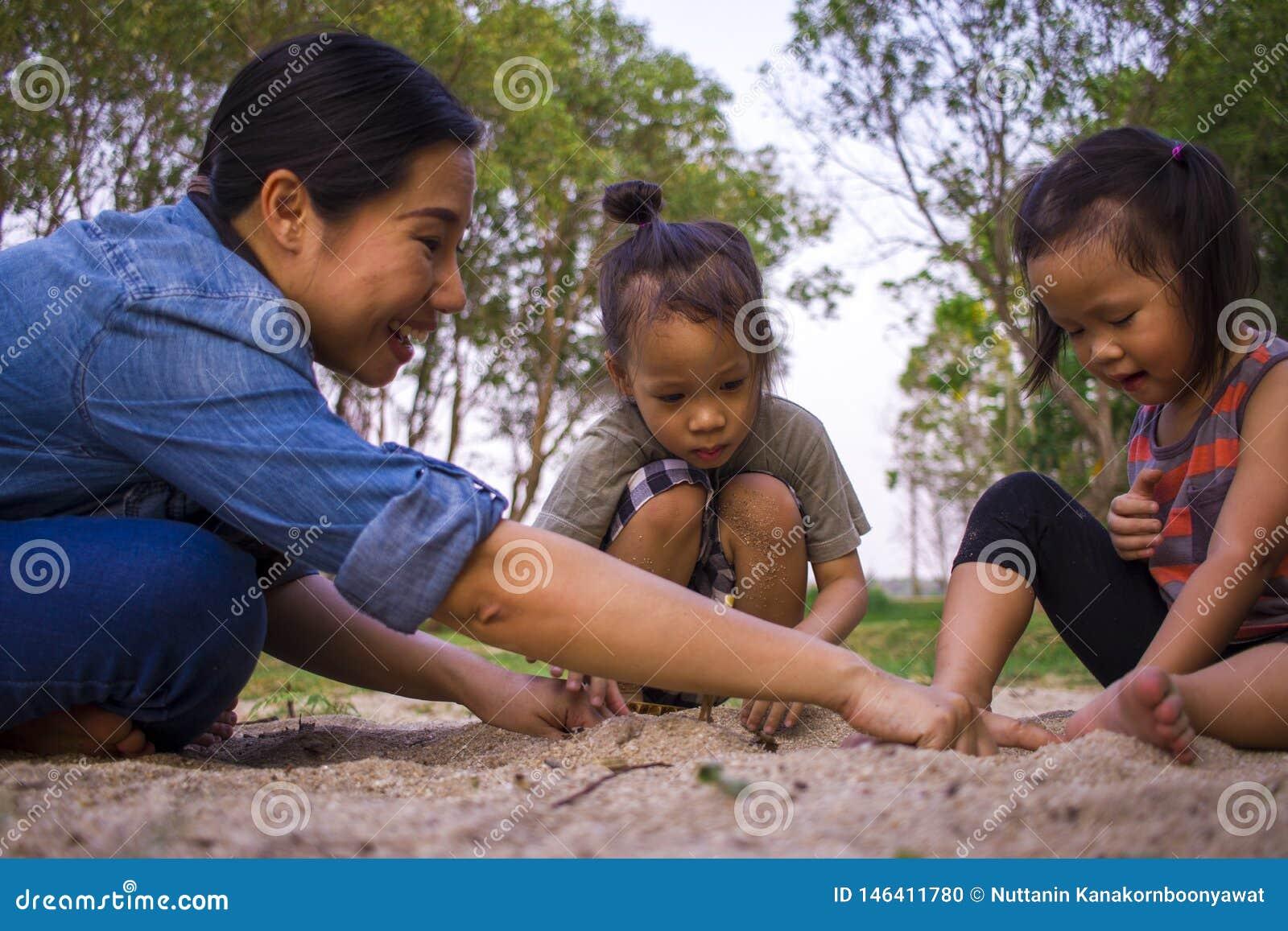 Van de het mammazoon en dochter van het levensstijlportret het spelen met zand, Grappige Aziatische familie in een park
