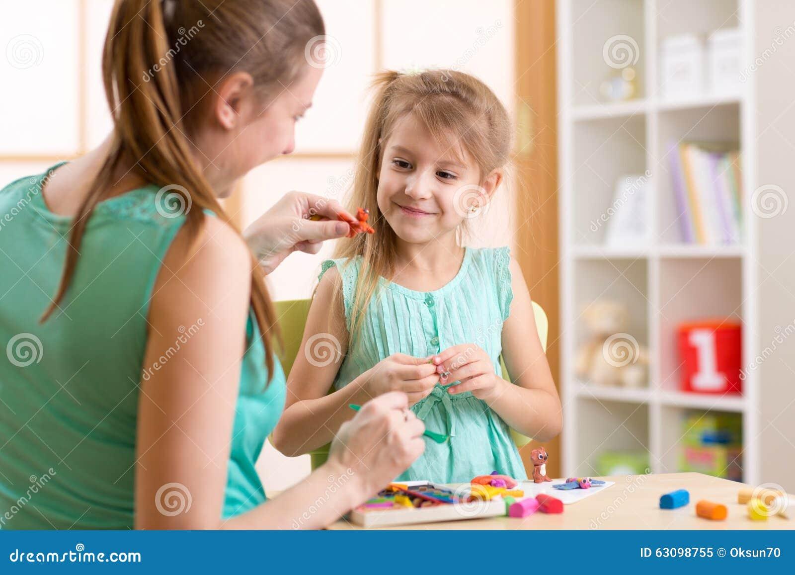 Van de jong geitjemeisje en moeder speelgoed van de spel het kleurrijke klei bij