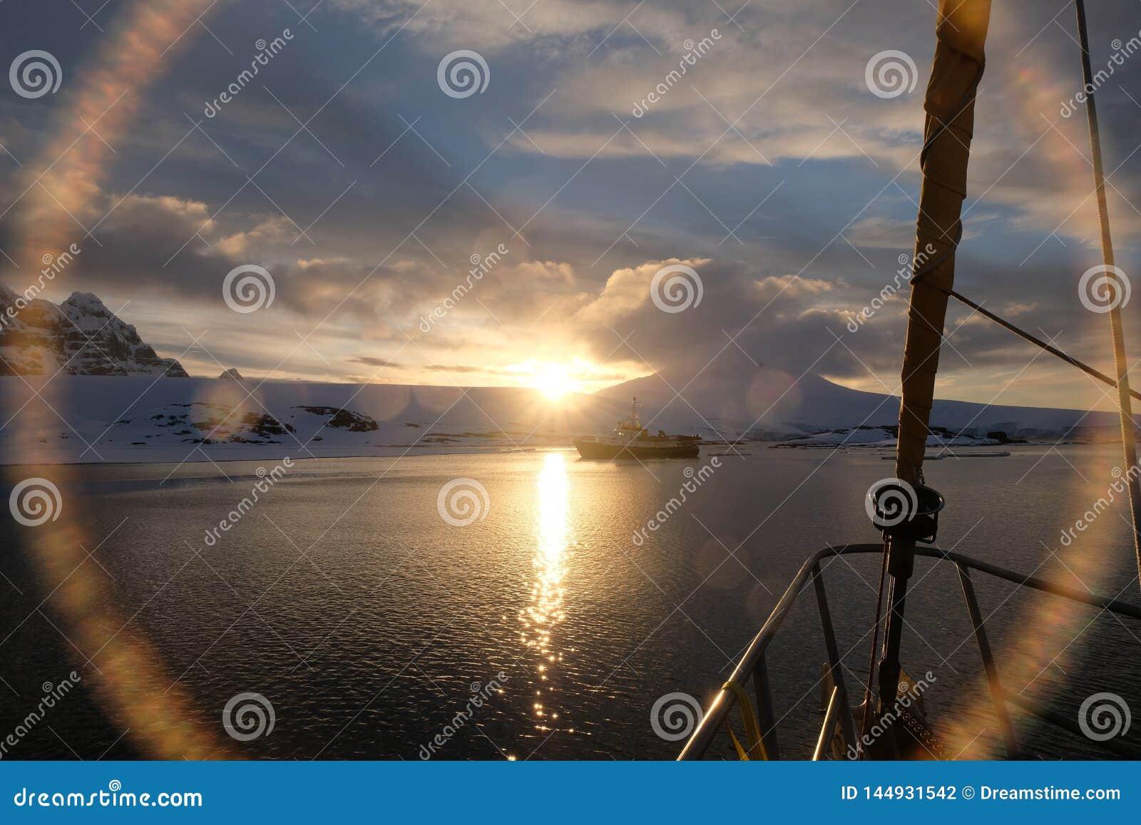 Van de de middernachtzonsondergang van Antarctica kalme de lensgloed van zeilboot