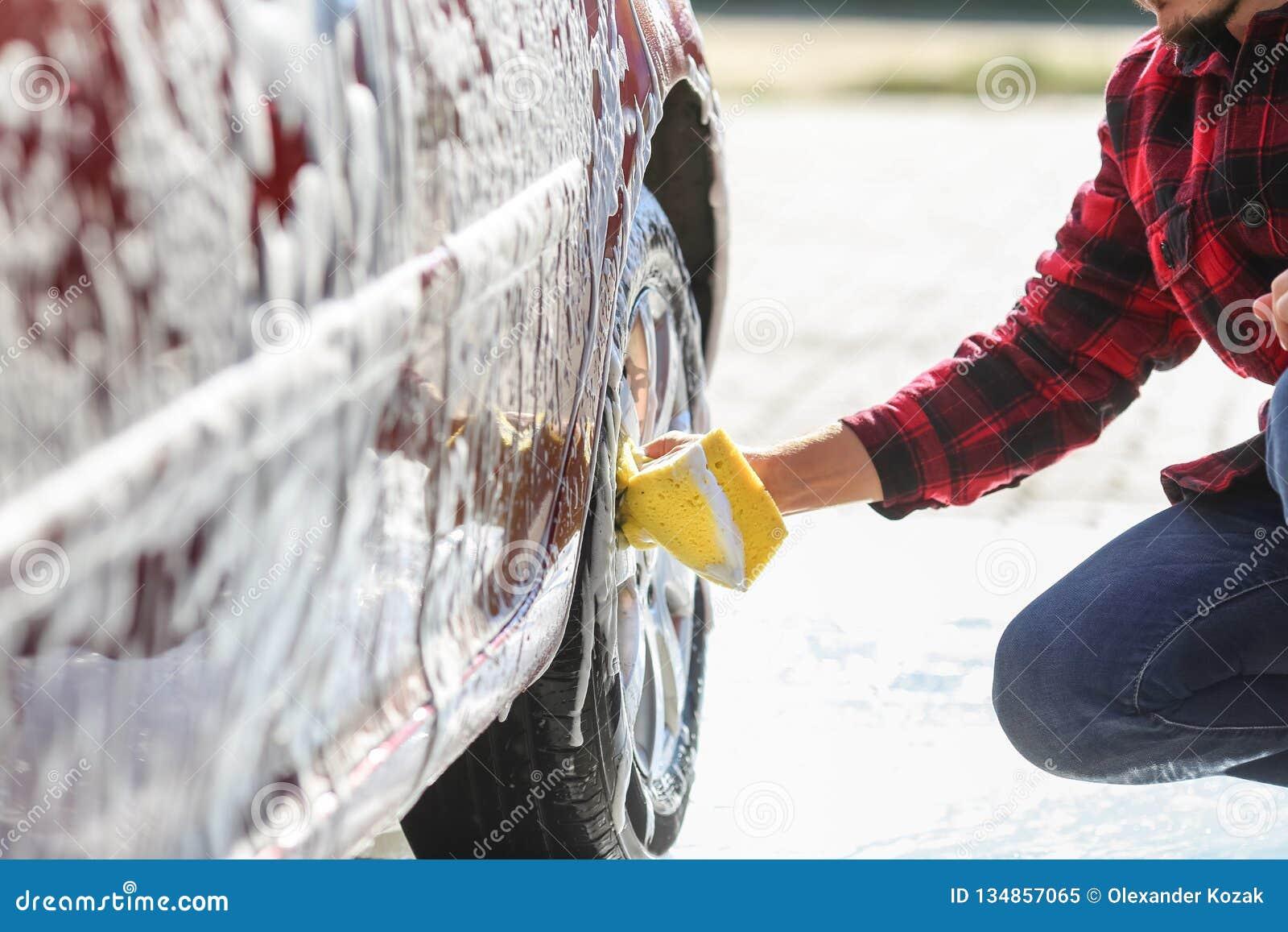 Van de de wasauto ` s van de mensenarbeider de legeringswielen op een autowasserette
