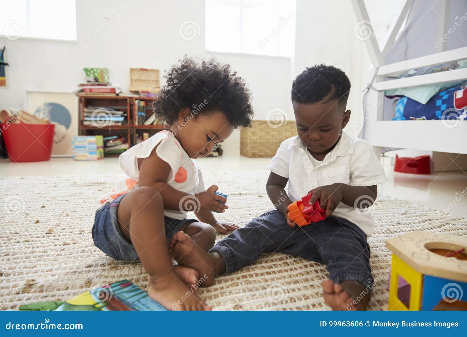 Van het babyjongen en Meisje het Spelen met Speelgoed in Speelkamer samen