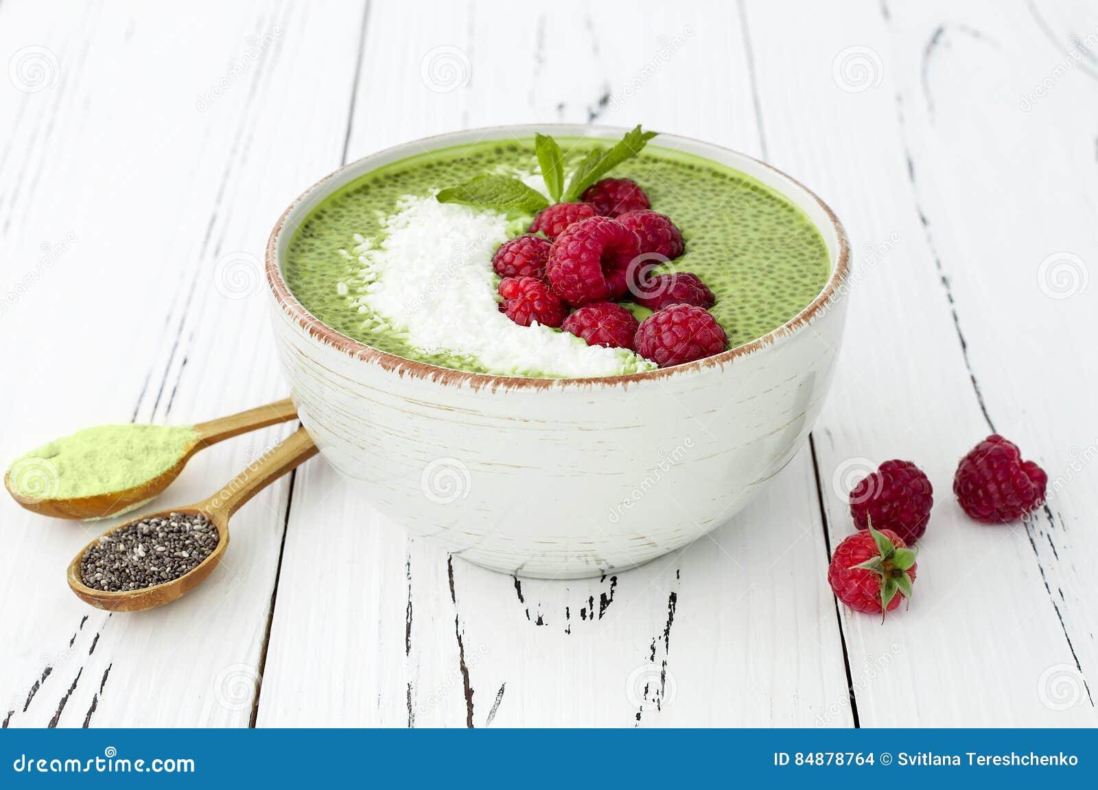 Van het chiazaad van de Matcha groene thee de puddingskom, veganistdessert met framboos en kokosmelk De lucht, hoogste vlakke men