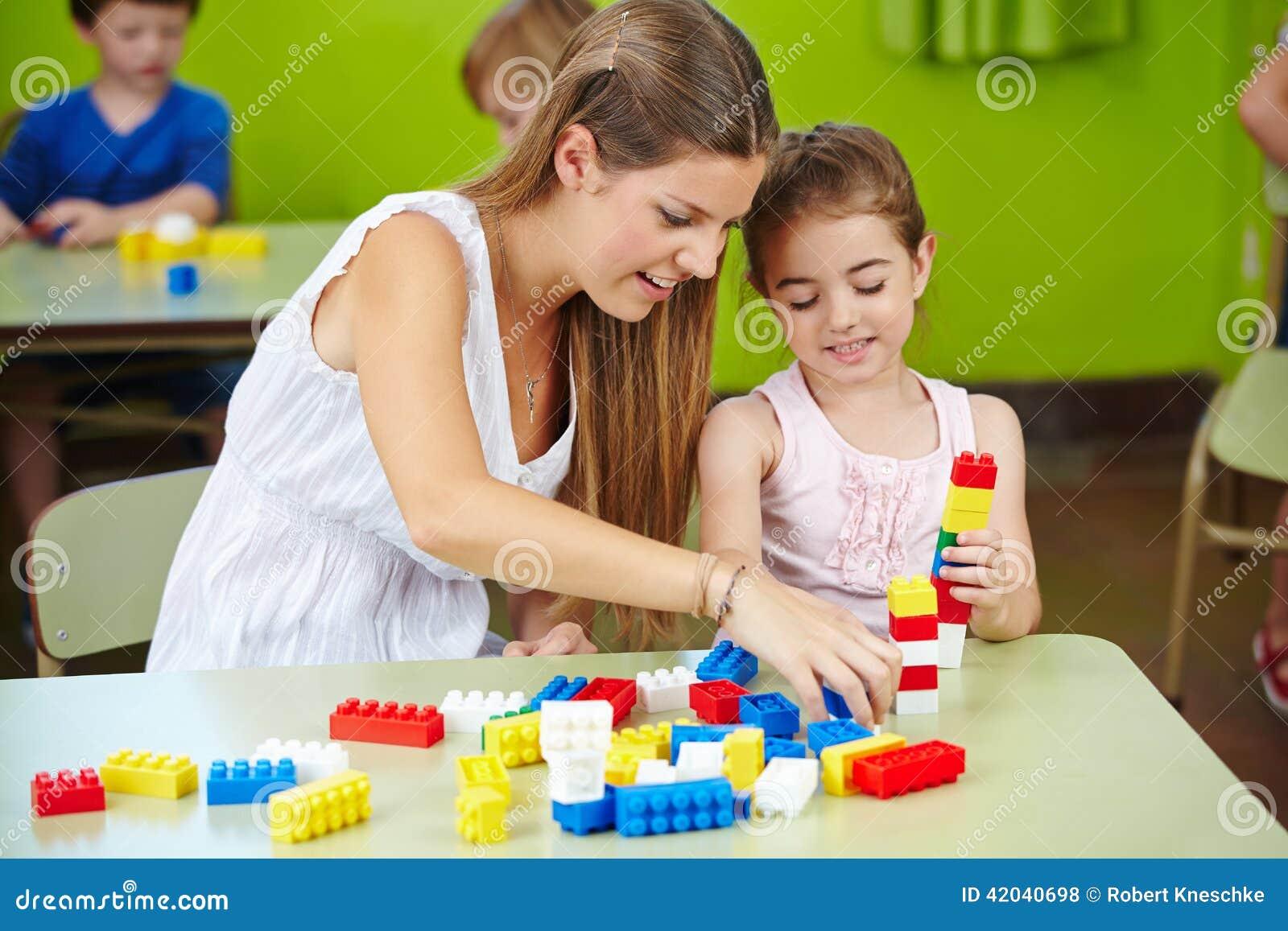 Van het kinderdagverblijfleraar en meisje het spelen