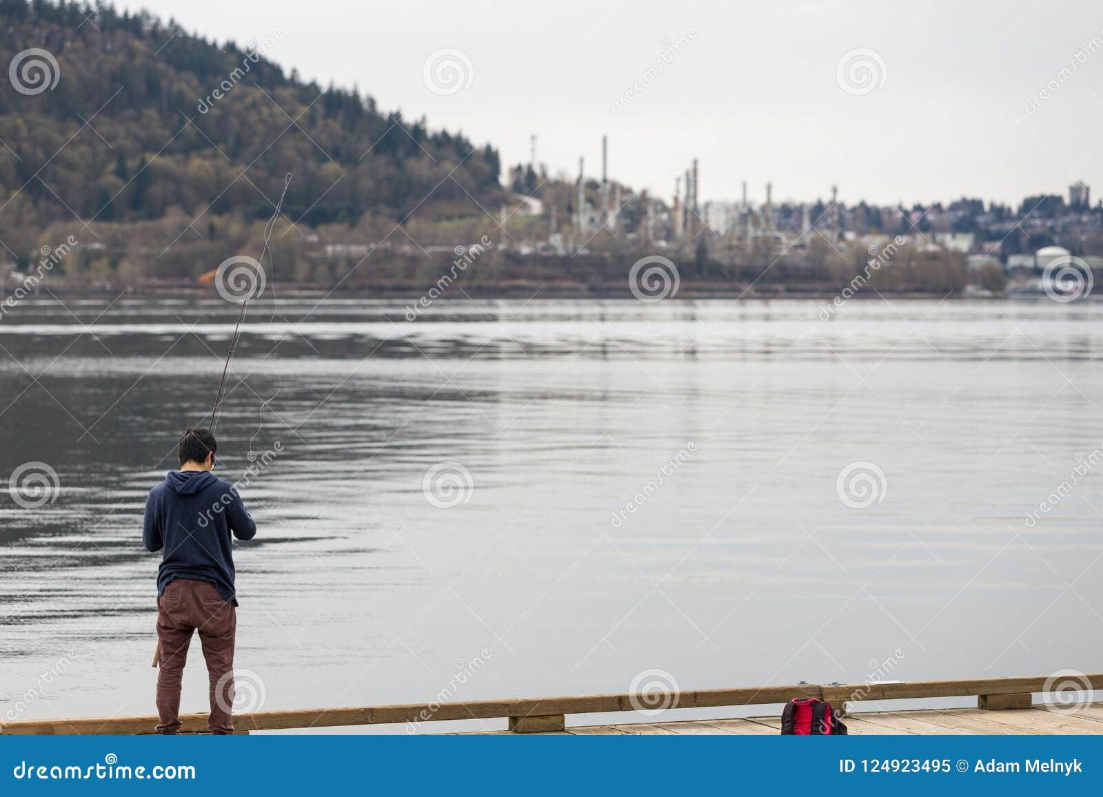 VANCÔVER NORTE, BC, CANADÁ - 9 DE ABRIL DE 2018: A refinaria do Parkland na montanha de Burnaby, com um homem que está em uma doc