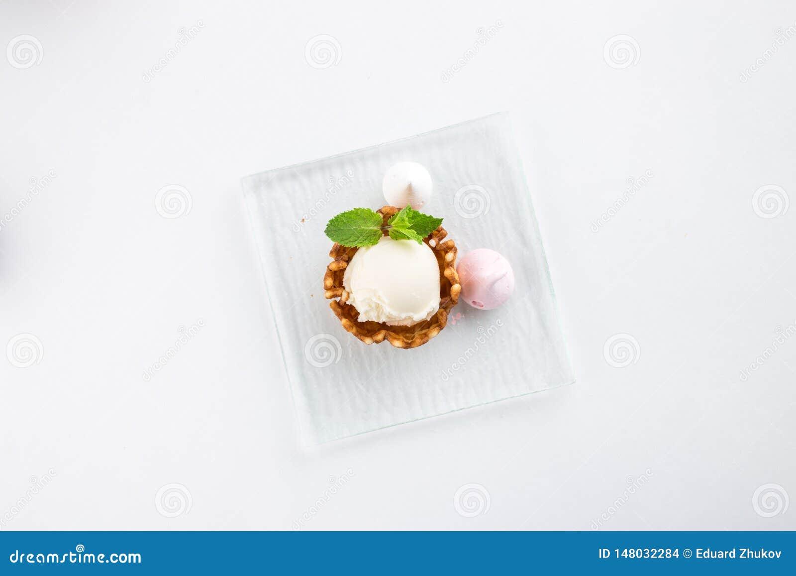 Vaniljglass med meringe och mintkaramell i en rånbunke som isoleras på vit bakgrund
