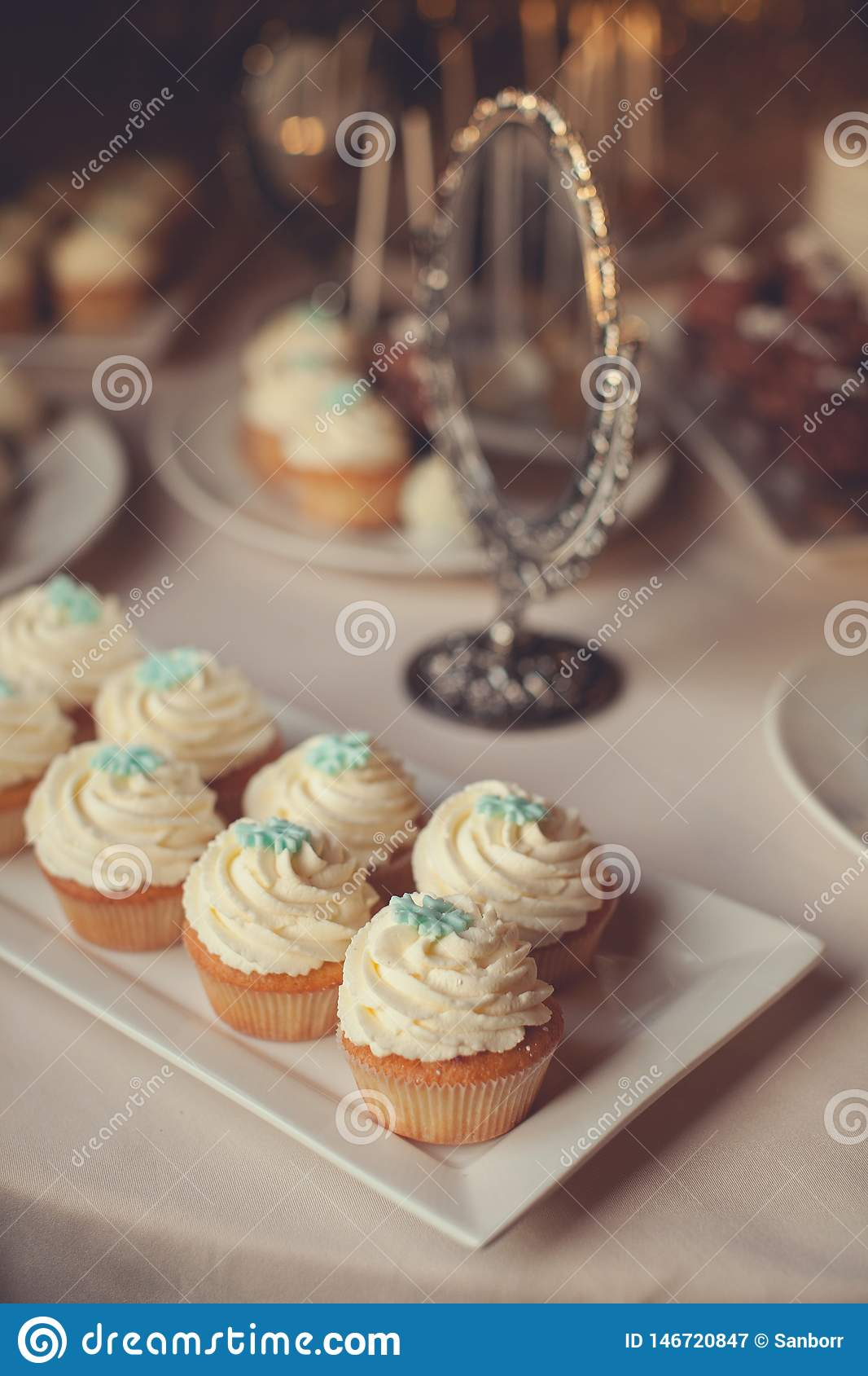Vanilla cupcakes with cream icing, decorated with decorative snowflake, close-up on a white glass dish, on a festive wedding table
