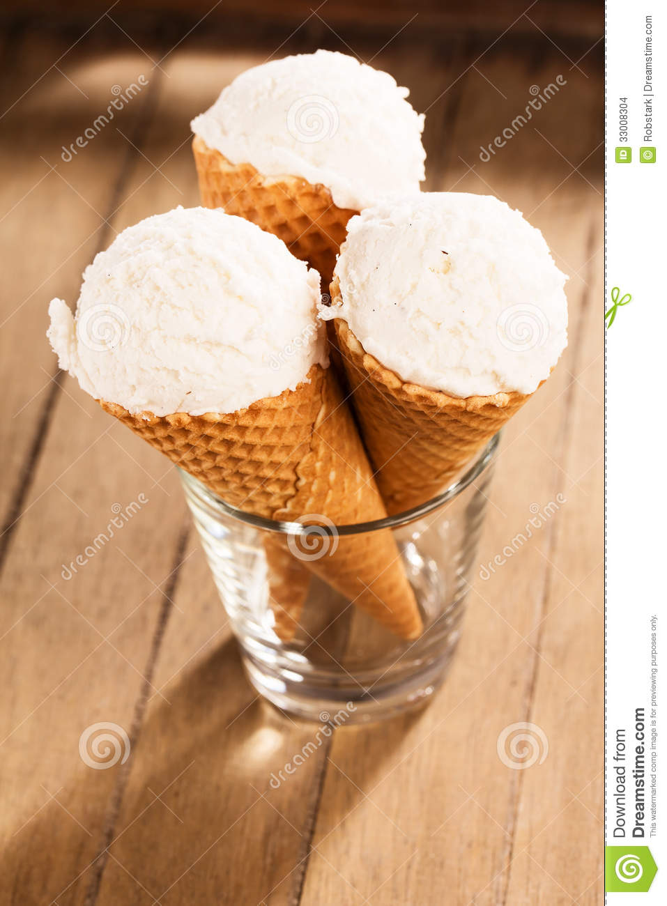 Three vanilla ice cream scoops in waffle cones standing in a glass on ...
