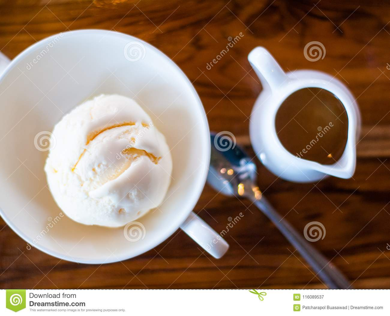 Vanilla icecream and a mug of espresso shot is placed together on coffee shop table
