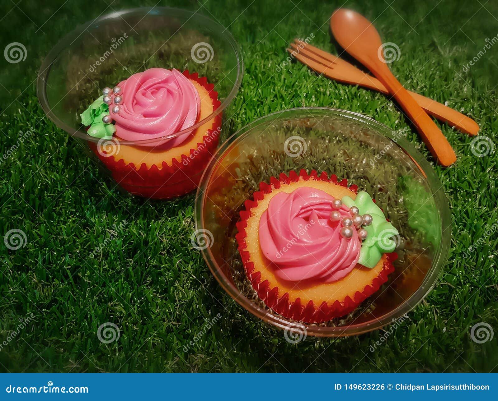 Vanille cupcakes in rode document koppen en duidelijke plastic koppen die met verse romige roze rozen worden verfraaid