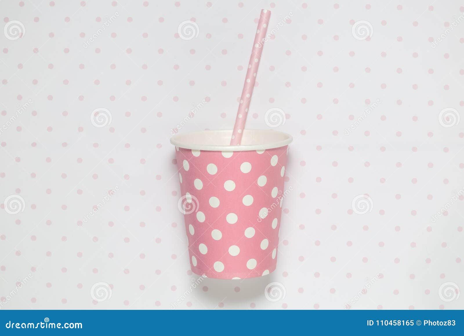 Vanlig rosa pappers- kopp med att dricka sugrör på polkatapeten