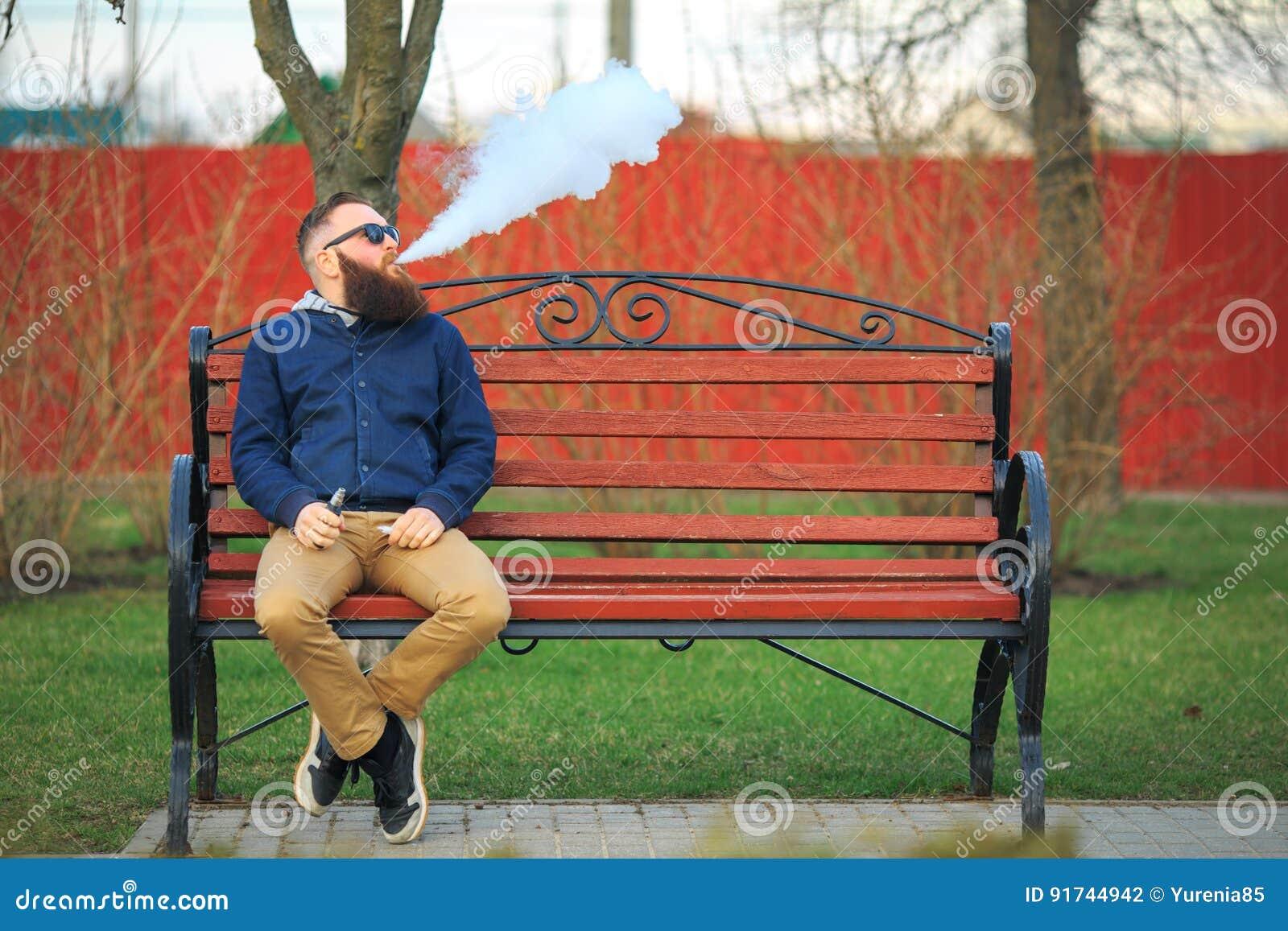 Vape 有大胡子和时兴的理发的年轻残酷人在太阳镜抽在红色长凳的一根电子香烟