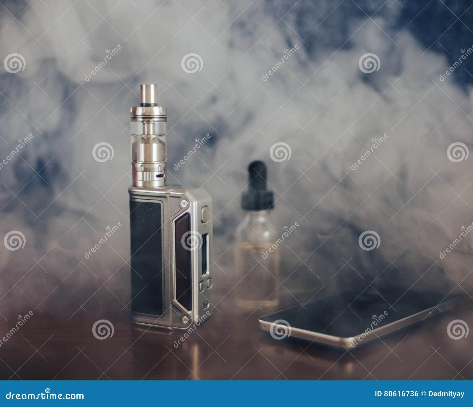 Vape przyrząda, papieros dla vaping, ciecz w butelce i telefon komórkowy,