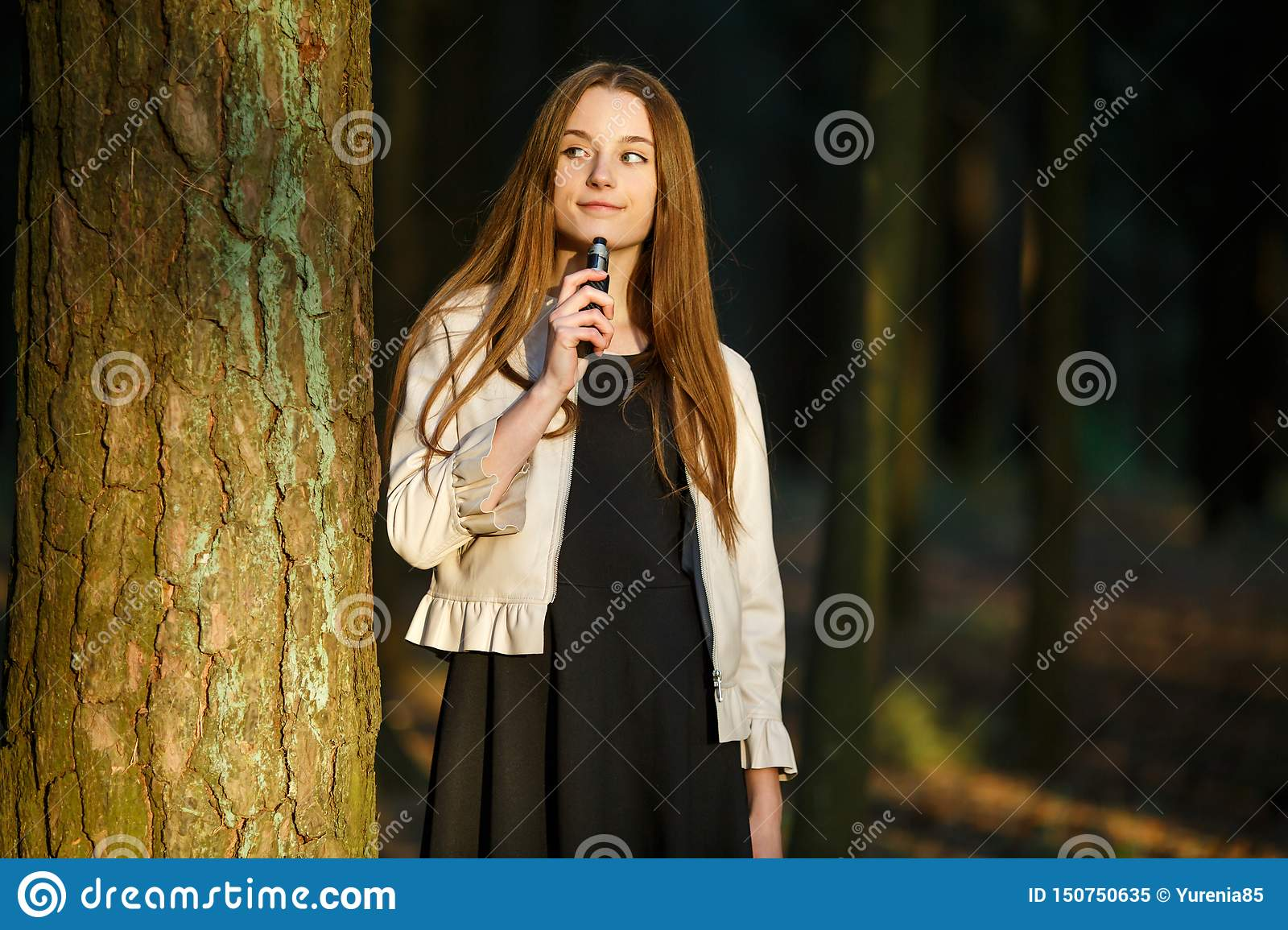 Vape teenager. Young cute girl in casual clothes smokes an electronic cigarette outdoors in the forest at sunset in summer.