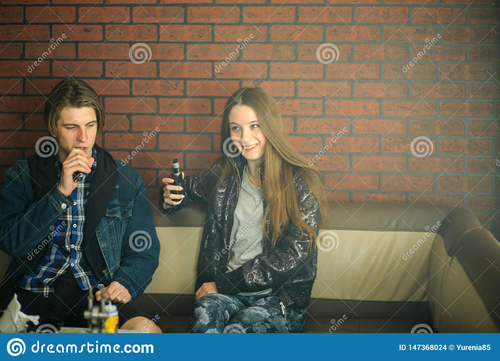 Vape teenagers. Young cute girl and young handsome guy smoke an electronic cigarettes in the vape bar. Bad habit