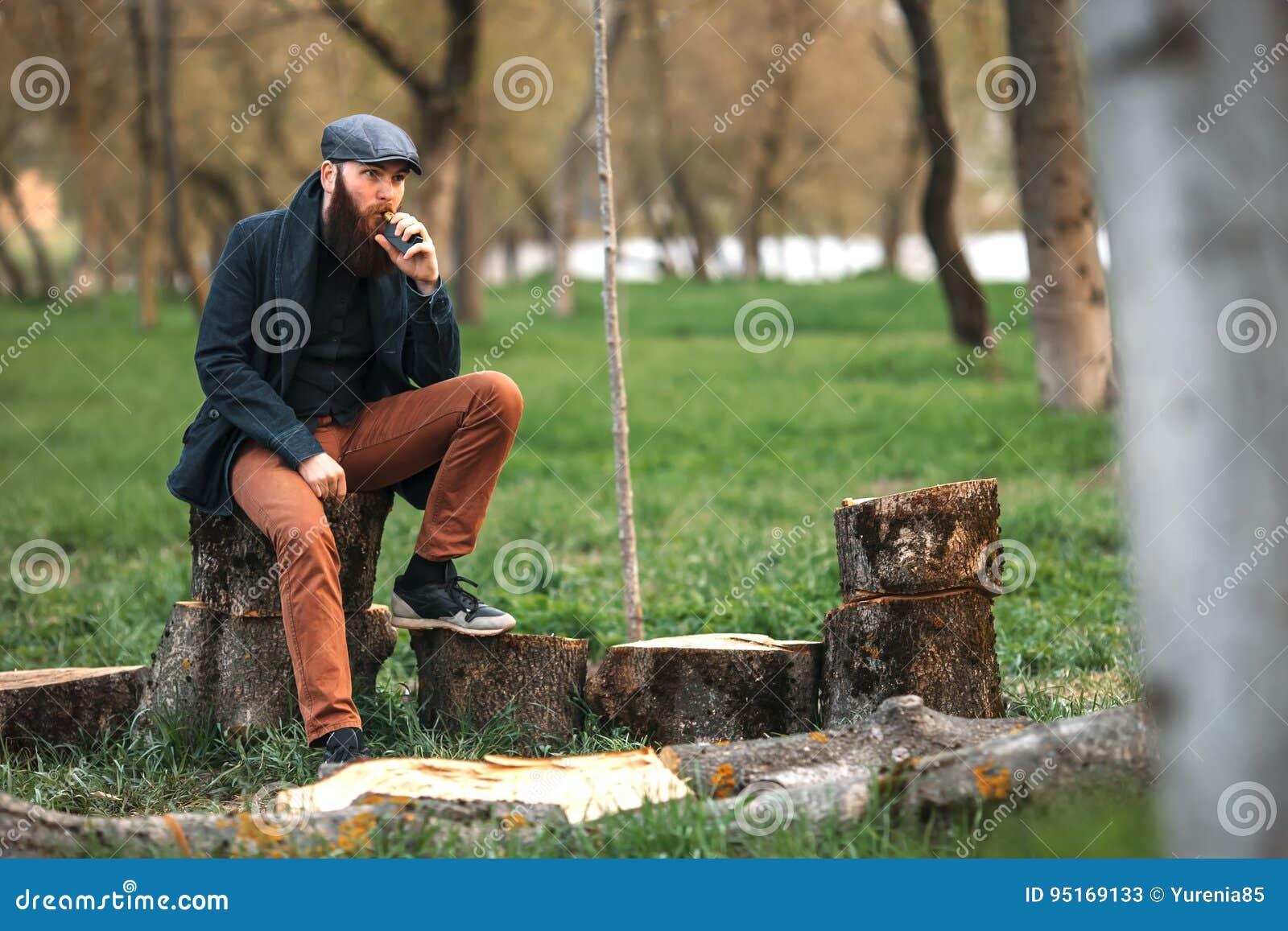 Vapemens Foto van een brutale gebaarde jonge mens die rust na karbonadebrandhout hebben en een elektronische sigaret in het dorp