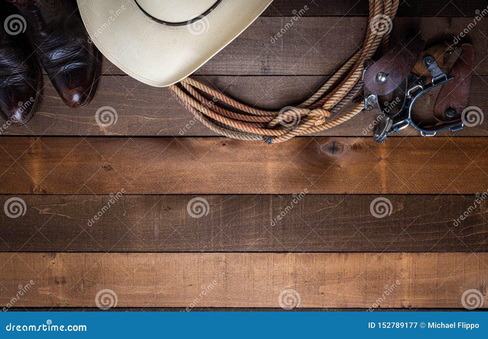 Vaquero americano Items estímulos incluing de un lazo y un sombrero de paja tradicional en un fondo de madera del tablón