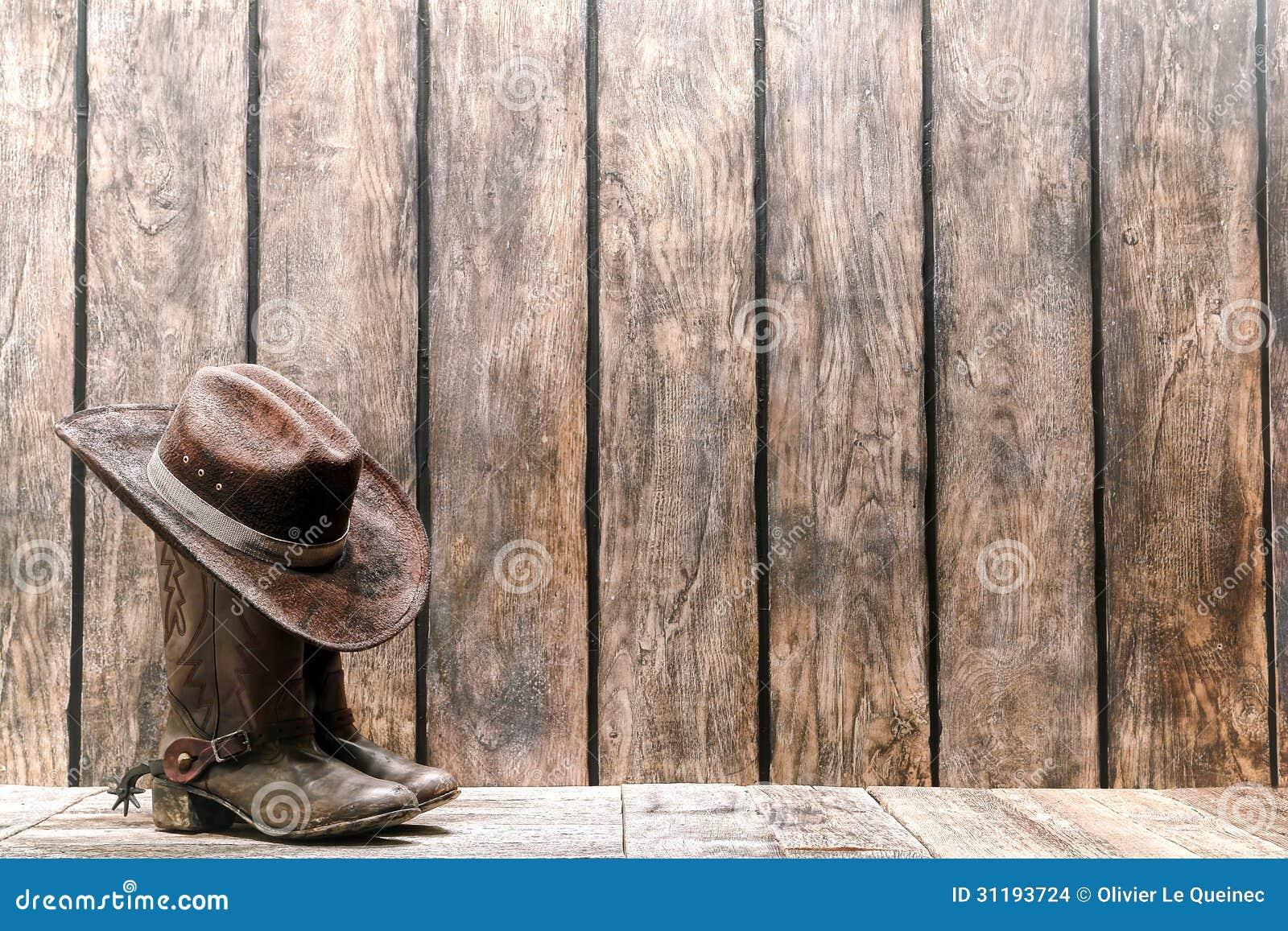 El marrón del oeste americano del rodeo sentía que sombrero de vaquero  encima de las botas de cuero tradicionales gastadas y sucias en una  cubierta de ... 726f0cfef54