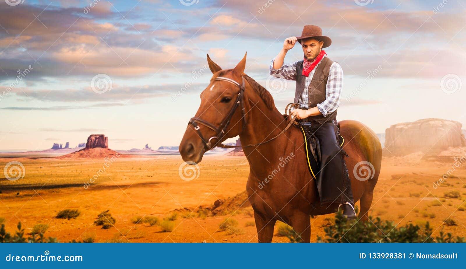 Vaquero que monta un caballo en el valle del desierto, occidental