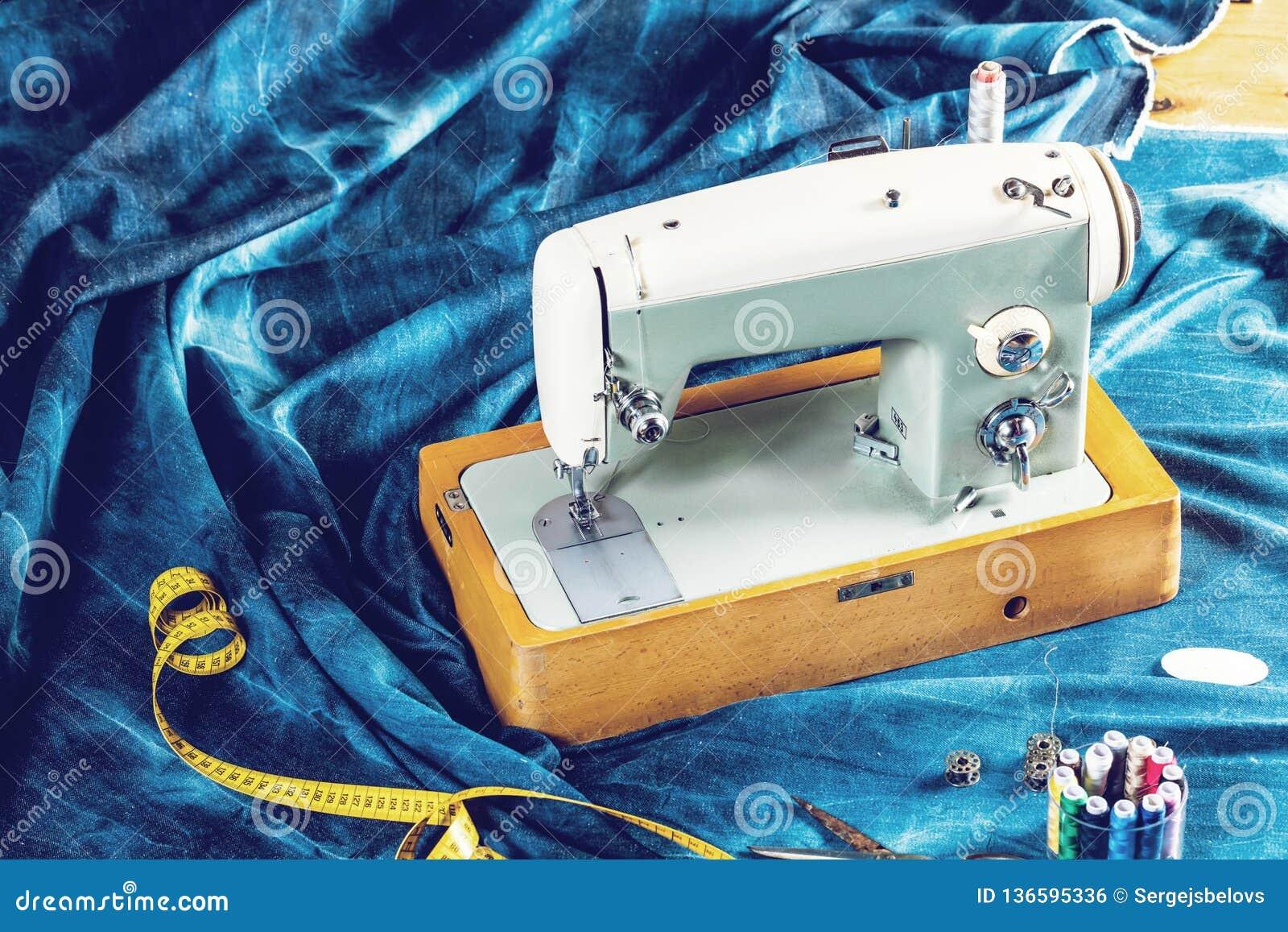 Vaqueros de costura con la máquina de coser, concepto industrial del dril de algodón del añil de la ropa