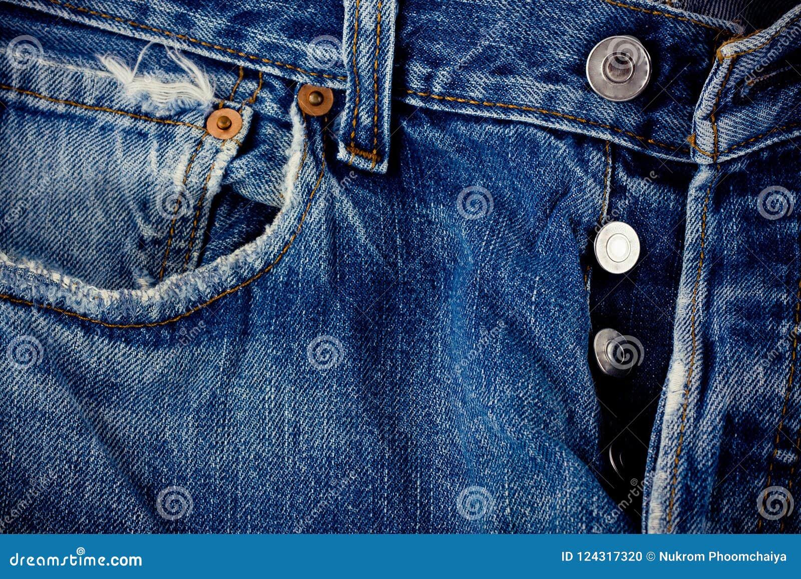 Vaqueros del botón de los vaqueros del fondo del denimand defectuoso y de la plata con una costura de la textura del dril de algo