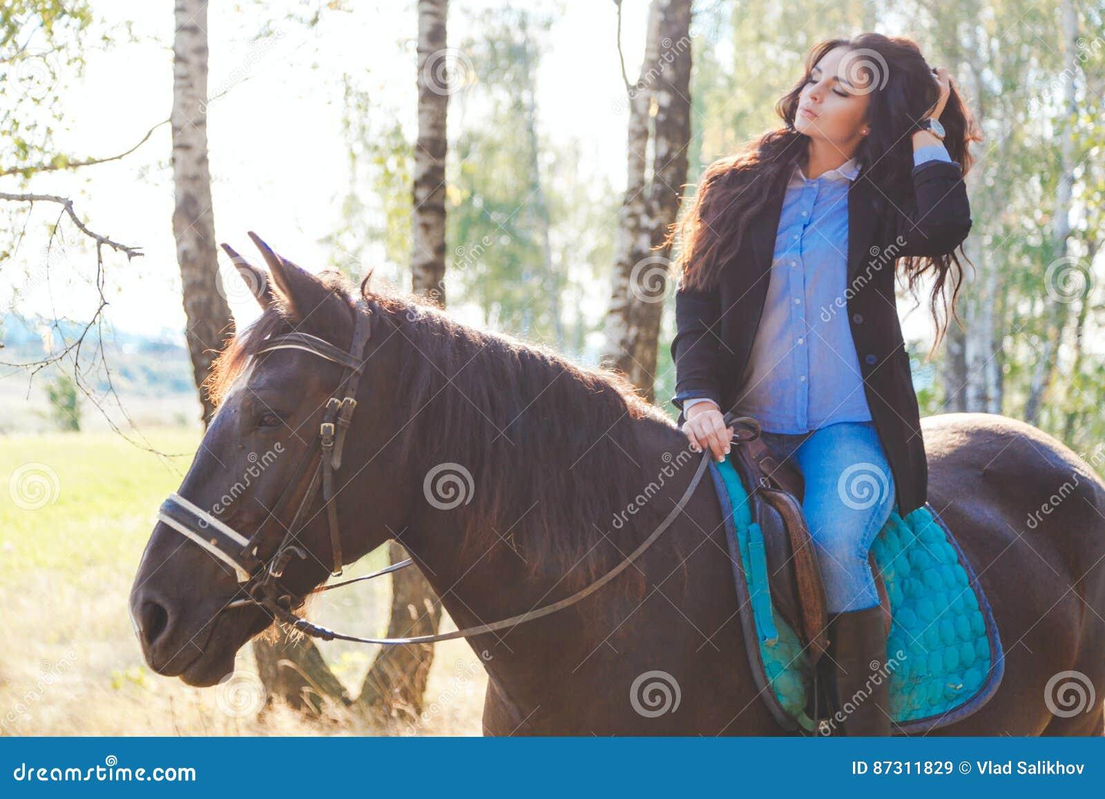 Vaqueros que llevan morenos atractivos hermosos, blusa y chaqueta negra montando un caballo en el día de verano soleado