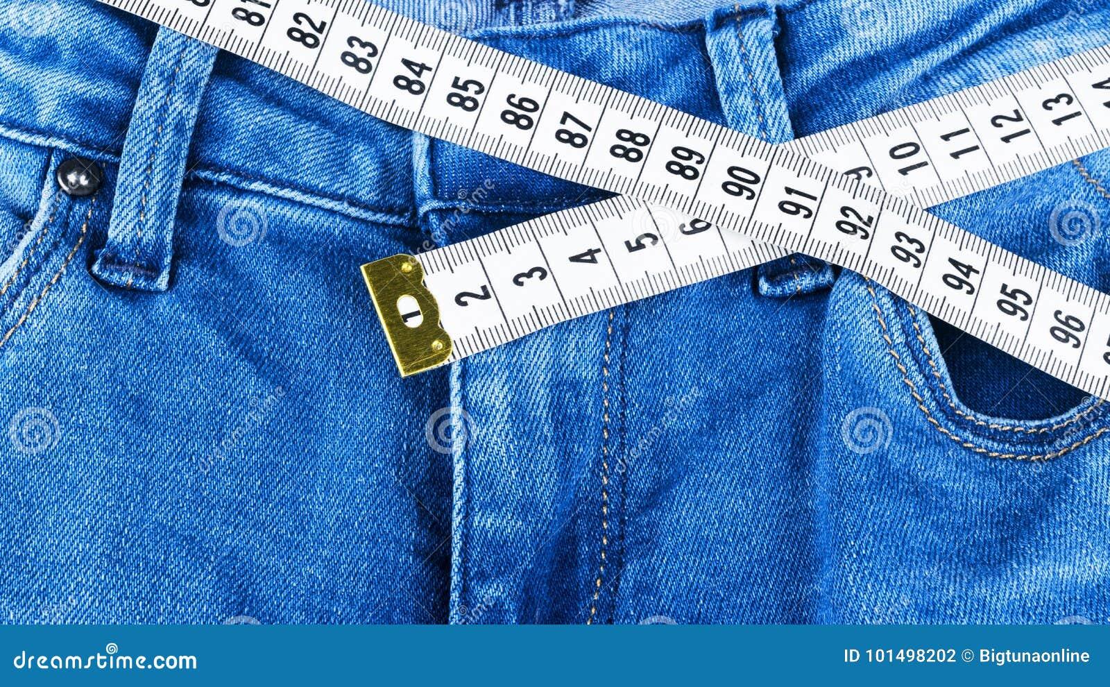 Vaqueros y una regla de la mujer del azul, concepto de dieta y pérdida de peso Vaqueros con la cinta métrica Forma de vida sana,