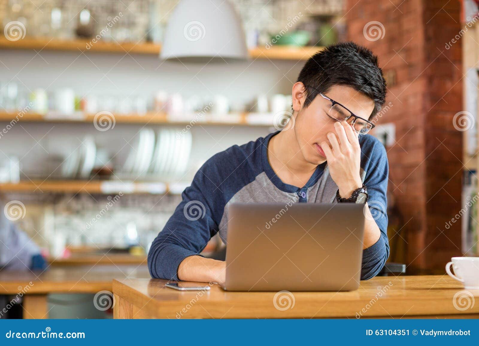 Varón asiático agotado cansado que trabaja con el ordenador portátil