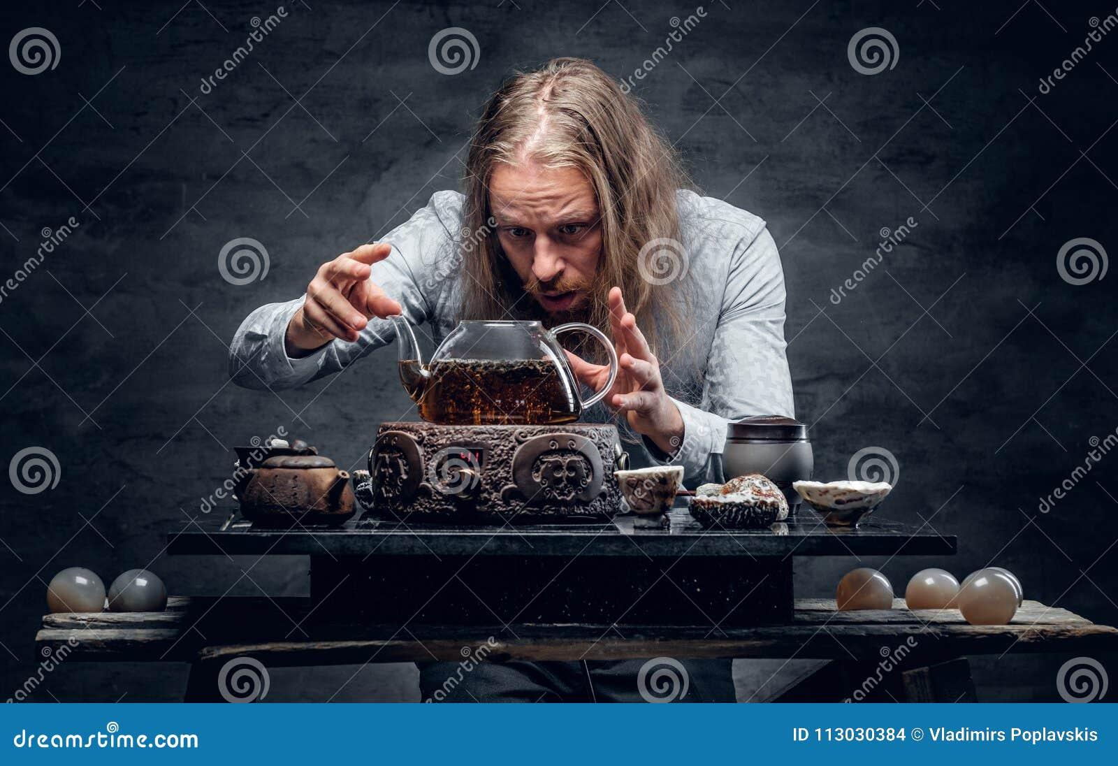 Varón barbudo con el pelo largo que prepara té