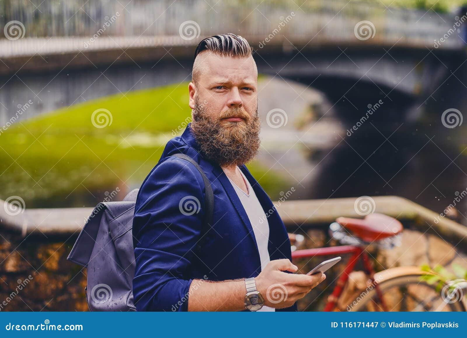 Varón del inconformista usando smartphone en un parque cerca del río