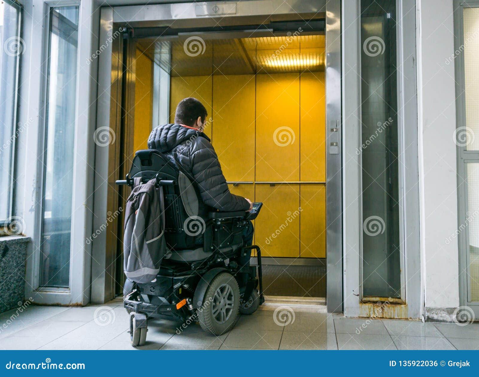 Varón perjudicado en la silla de ruedas que entra en elevador