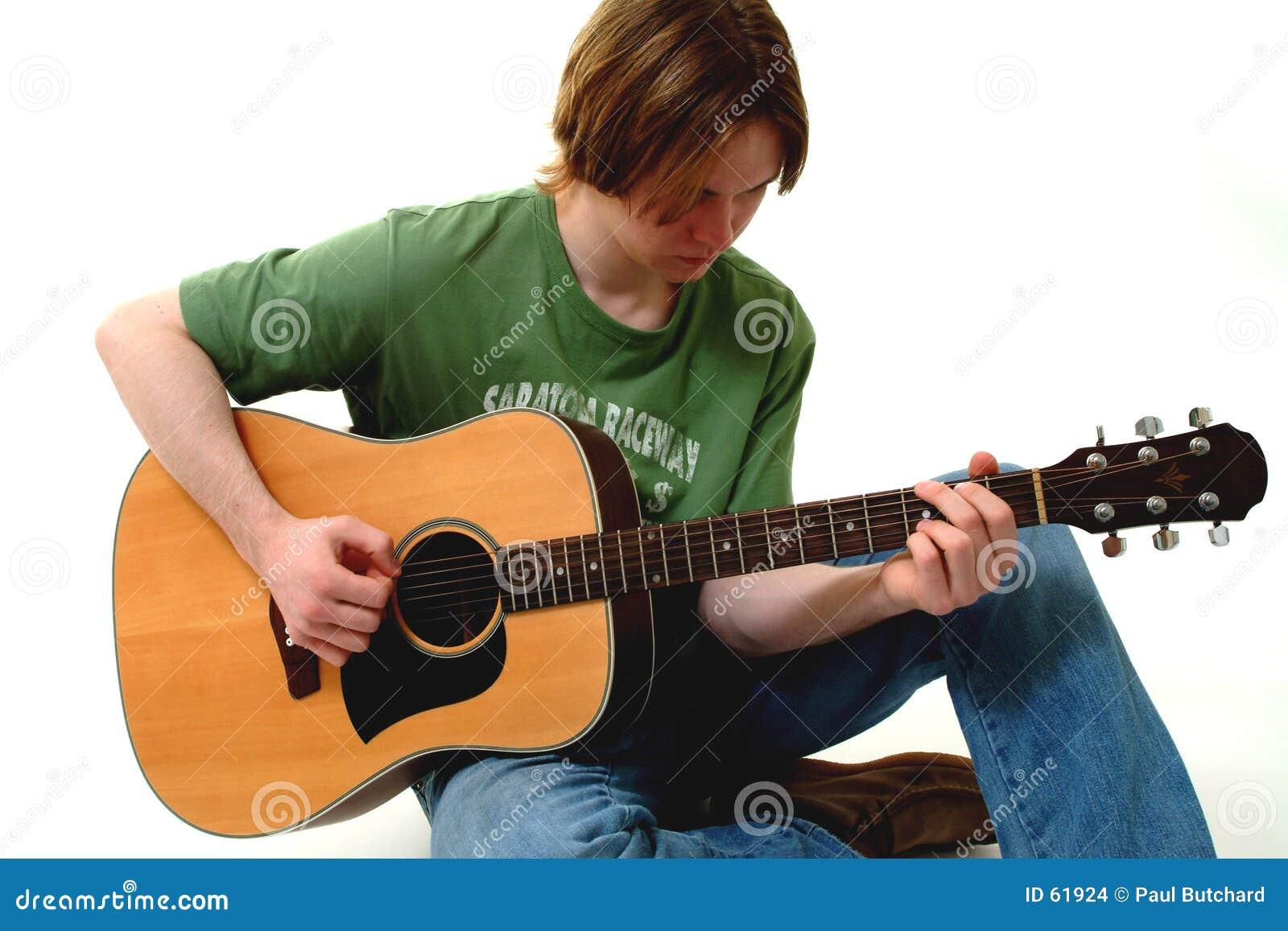 Varón que toca la guitarra acústica