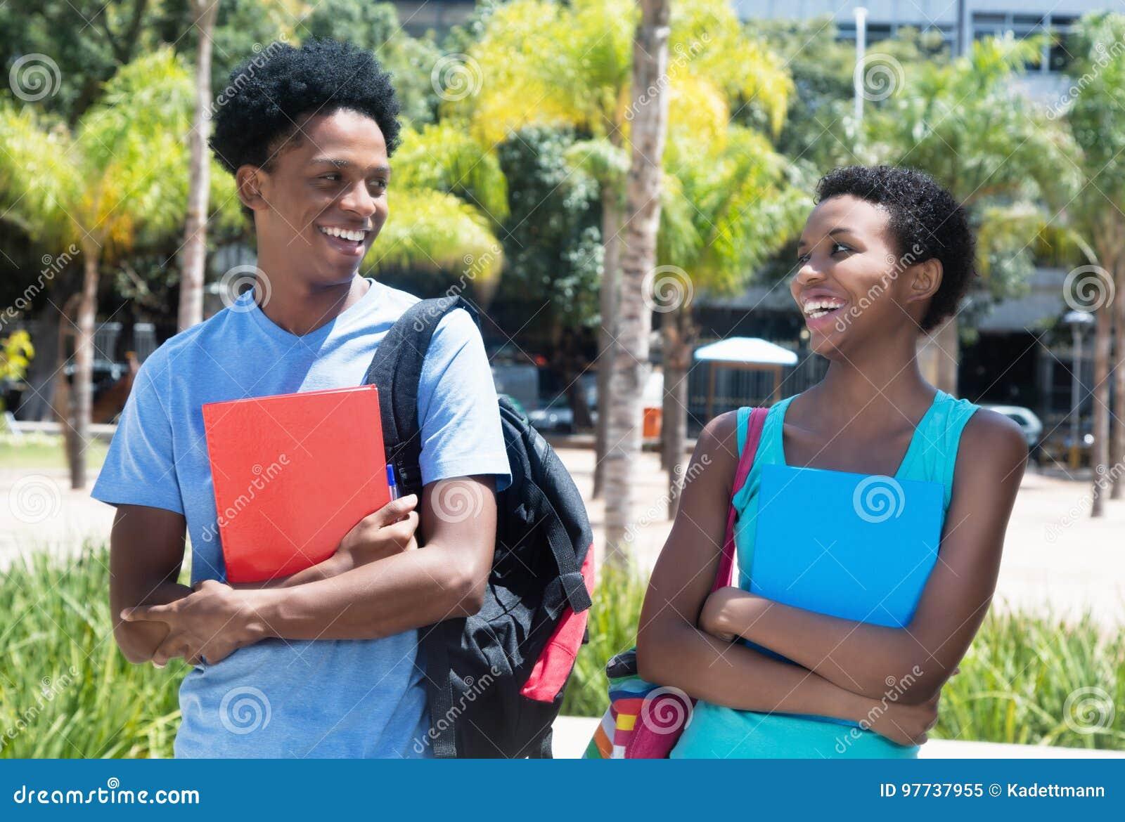 Varón y estudiante afroamericanos de risa en el campus de u