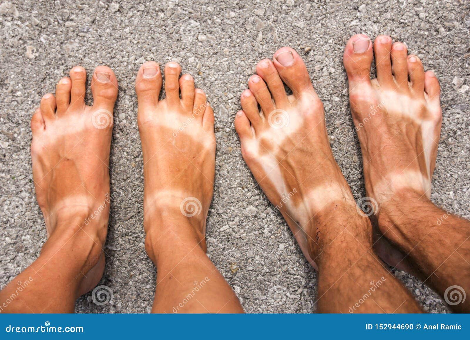 Varón y pies bronceados femeninos