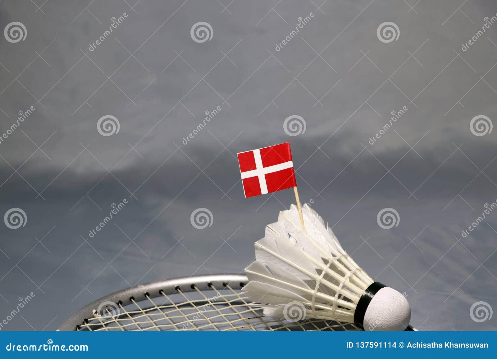 Vara da bandeira de Mini Denmark na peteca posta sobre a rede da raquete de badminton no assoalho cinzento