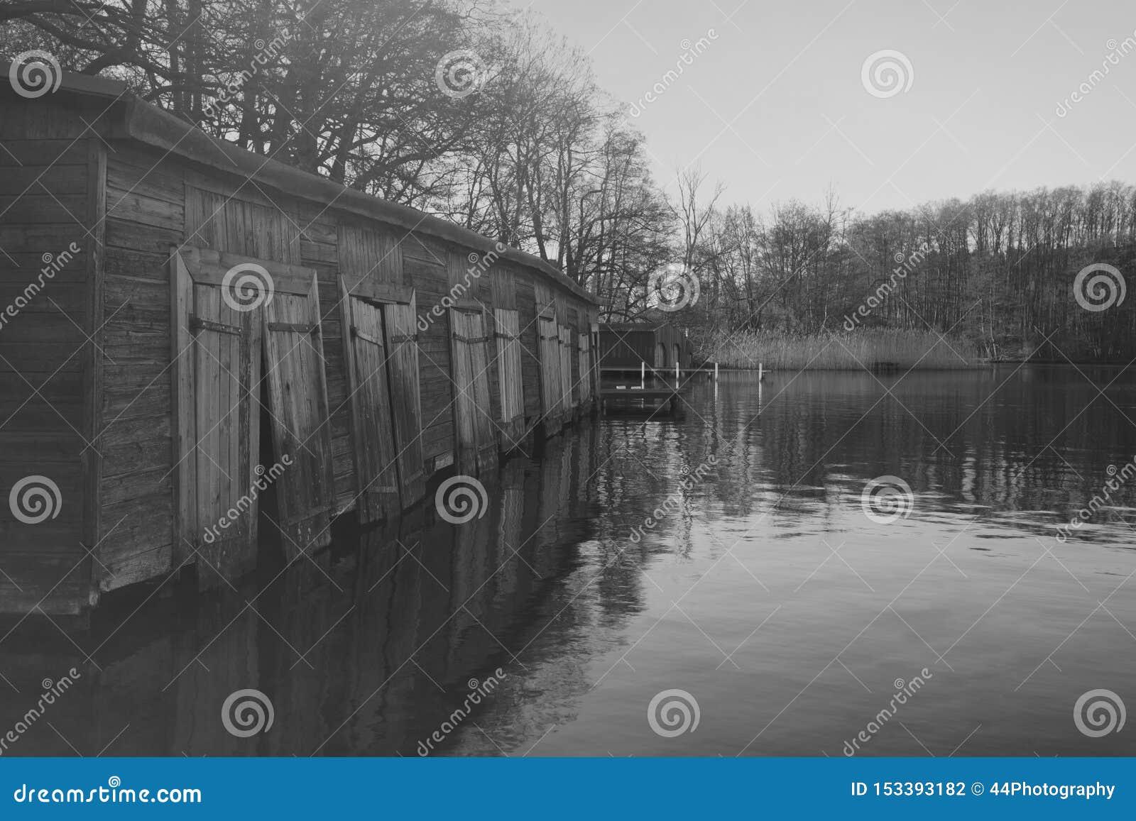 Varadero de madera viejo en el lago en la niebla de la madrugada, fotografía blanco y negro