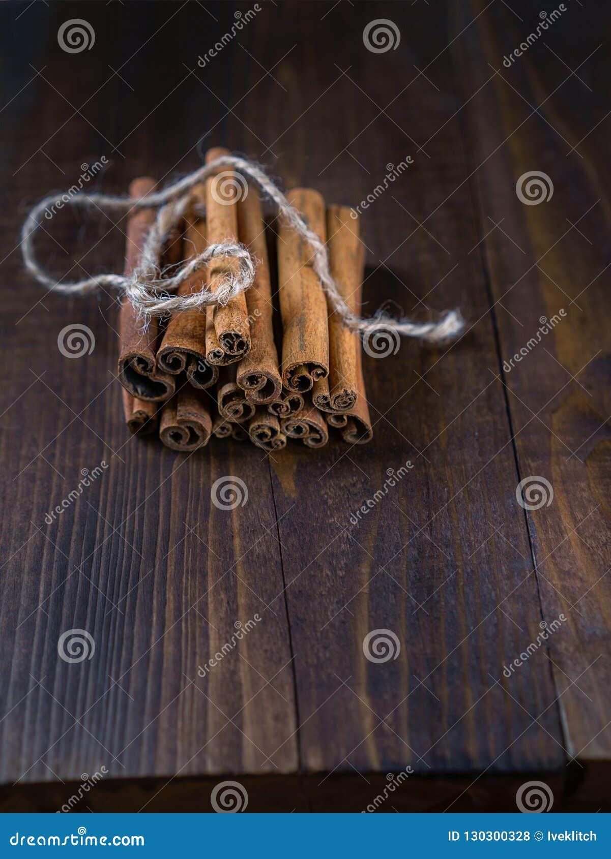 Varas de canela amarradas com corda da juta no fundo de madeira velho no estilo rústico