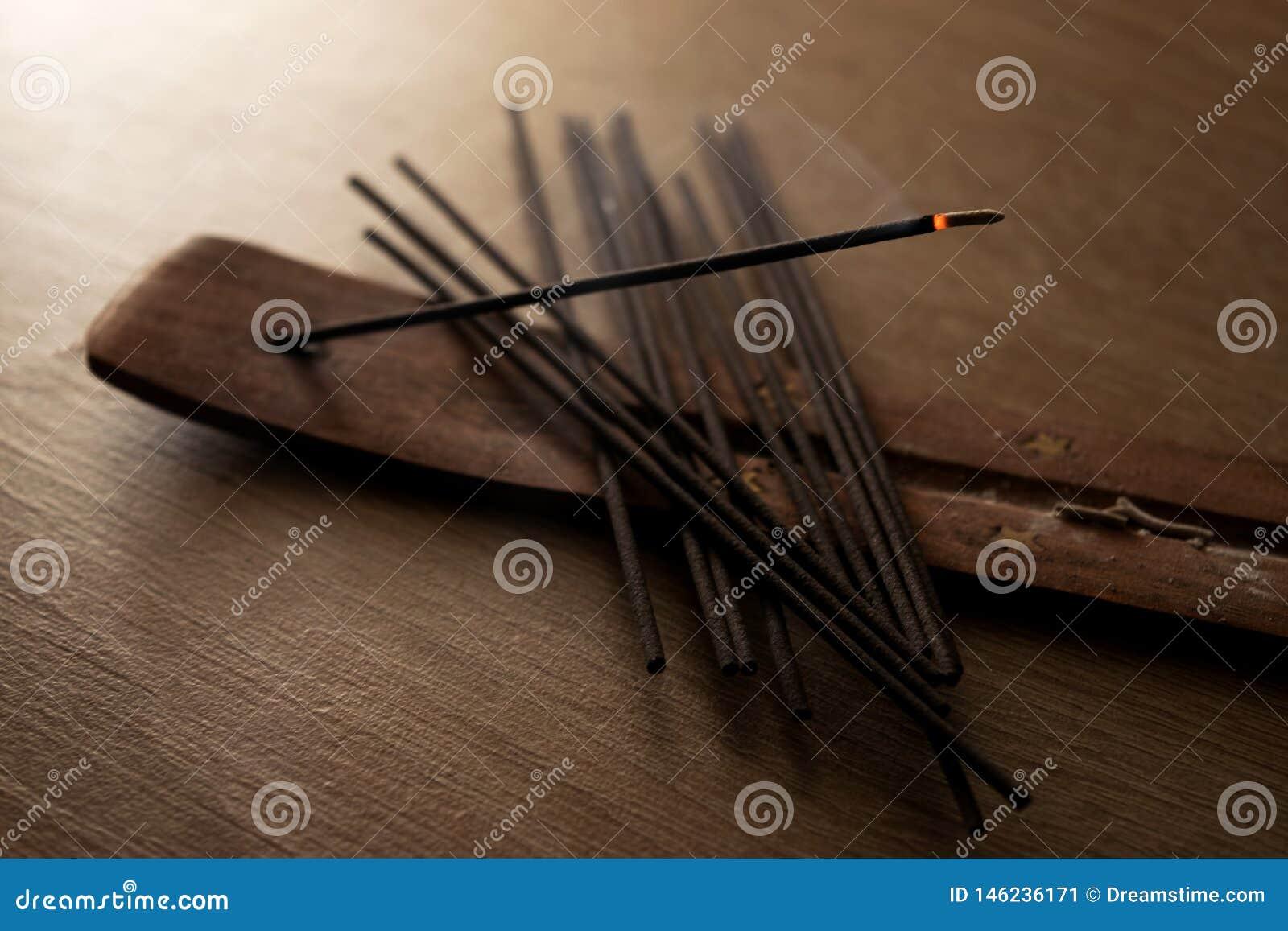 Varas do incenso no fundo de madeira
