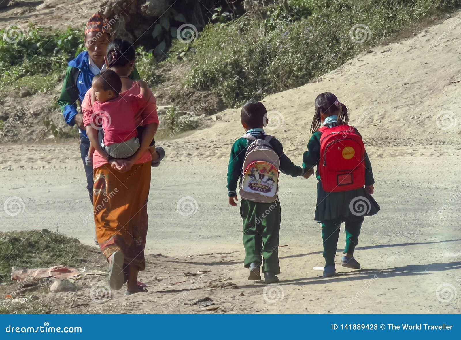 Vardagsliv i Nepal, barn i likformig går handen - i - handen till skola, moder bär ett småbarn på hennes baksida
