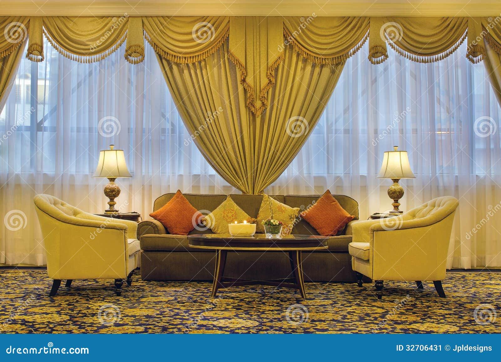 Vardagsrum med utsmyckade gardiner och möblemang fotografering för ...
