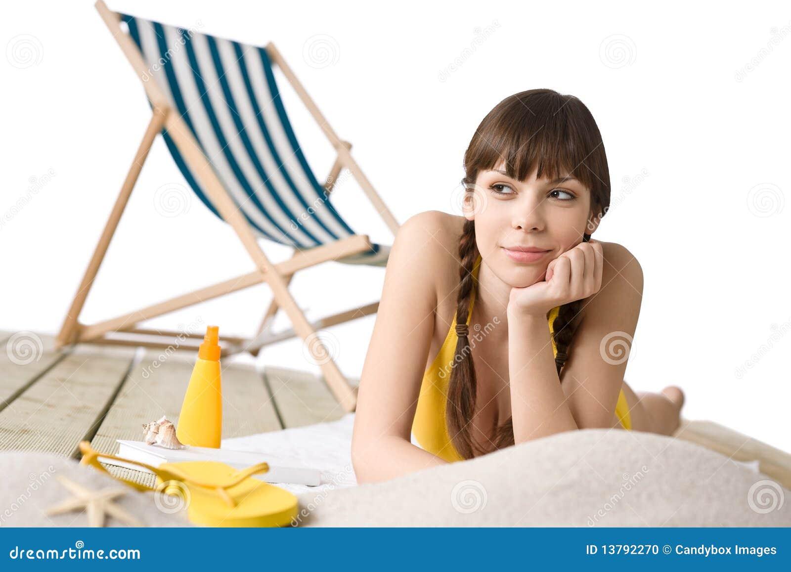 Vare con la silla de cubierta - mujer en bikiní que toma el sol