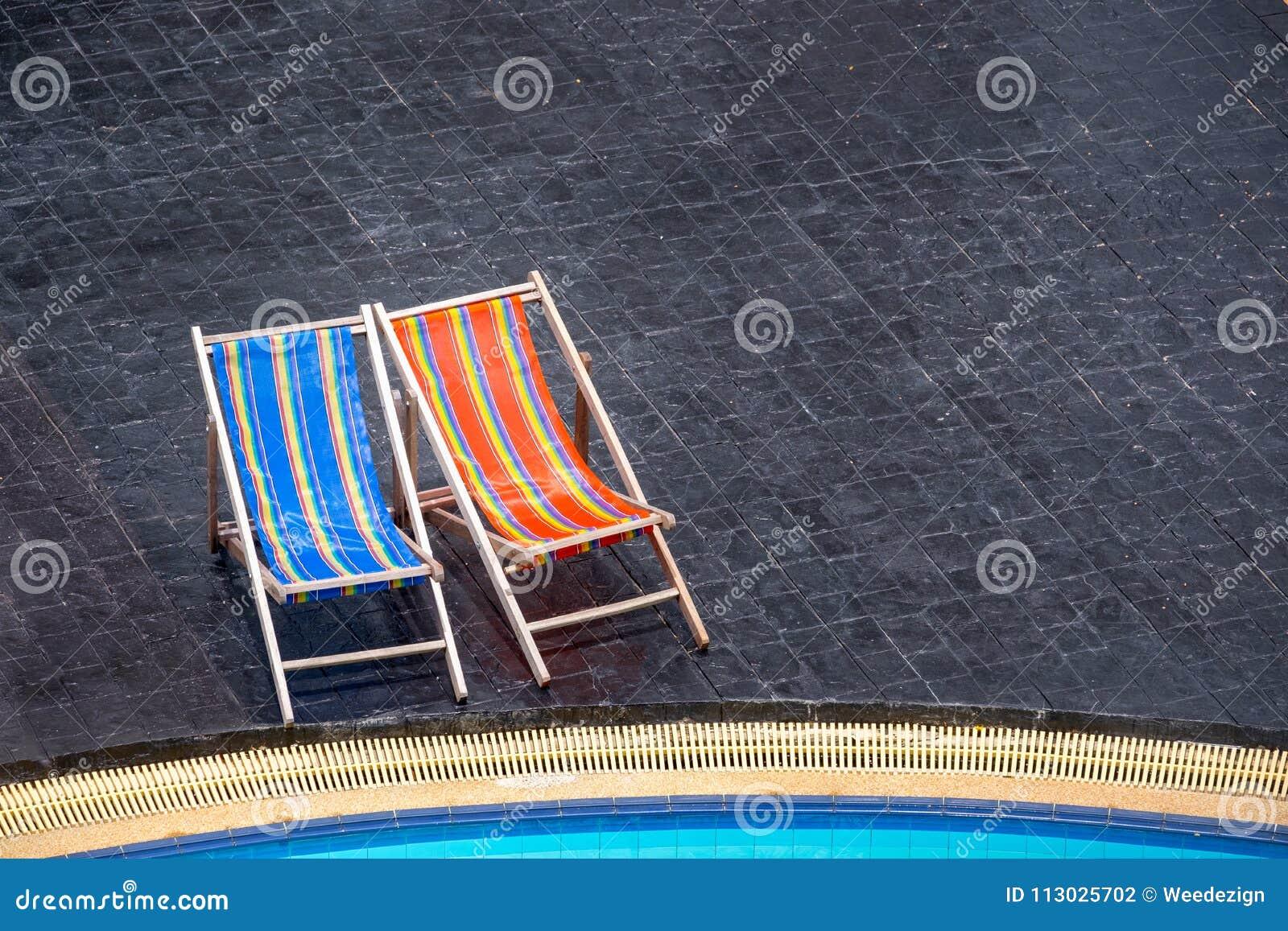 Vare el banco en la teja negra en la piscina Vacati de las vacaciones de verano